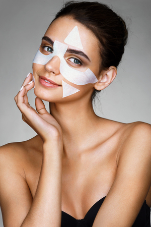 face mask: Charming young woman with cotton facial mask. Photo of brunette touching hand her face. Skin care concept.