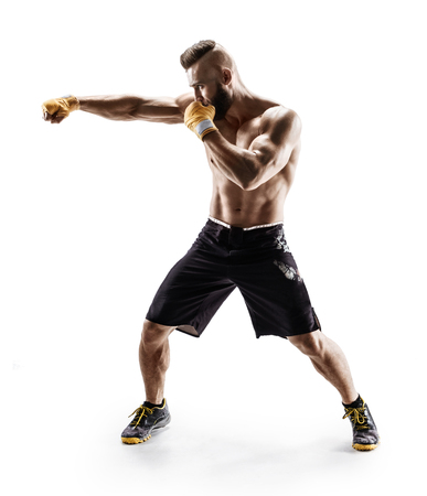 Muscular male in sports clothes ?onducts fight with shadow. Photo of boxer on white background. Strength and motivation
