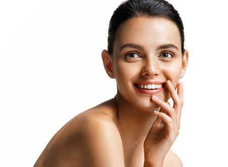 Smiling happy girl sitting over white background. Photo of pretty girl with slim toned body. Beauty & Skin care concept Archivio Fotografico
