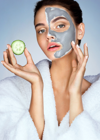 Beautiful sensual girl with the slice of cucumber in hand on blue background. Photo of girl in white bathrobe and with mask of clay on face. Grooming himself