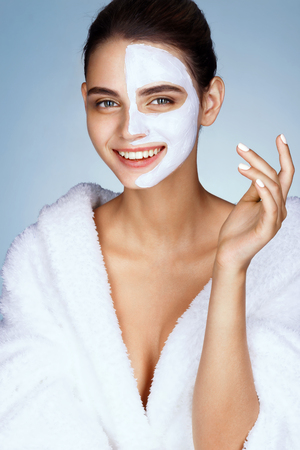 brunette girl: Smiling young girl with cosmetic mask on her face. Photo of beautiful brunette girl wearing white bathrobe. Wellness and Spa concept