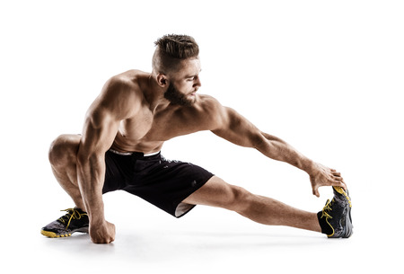Man stretching his hamstrings. Photo of sporty man doing exercising on white background. Sports