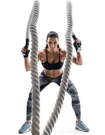 強い筋肉の女性は重いロープでワークアウトします。スポーツウェアは、白い背景で隔離の魅力的な女性の写真。強さと動機。
