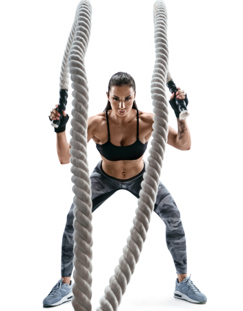 Sterke gespierde vrouw uit te werken met zware touwen. Foto van aantrekkelijke vrouw in sportkleding die op witte achtergrond wordt geïsoleerd. Kracht en motivatie. Stockfoto
