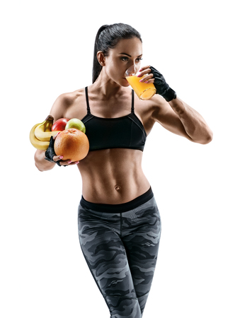 Resting time. Attractive young woman in sports wear hold fresh fruits and drink  orange juice. Organic food and health concept. Stock Photo