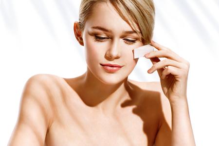 Charmant meisje aanbrengen stichting op haar gezicht met make-up spons. Foto meisje op witte achtergrond met palmblad schaduwen. Perfecte make-up