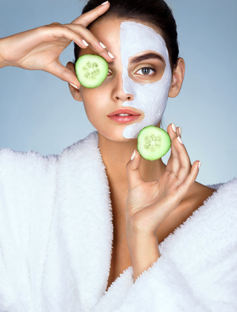 Attractive girl holding cucumber slices up to her eyes. Photo of girl with moisturizing facial mask. Beauty & Skin care concept