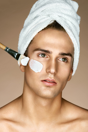 Beautician is applying facial cream on his skin. Fashionable man receiving spa treatments. Grooming himself