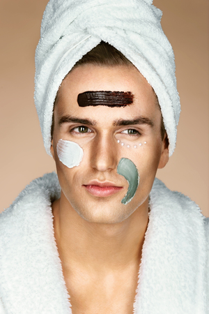 Fashionable man with three different face masks (chocolate, cream and clay masks). Photo of man with perfect skin. Grooming himself Stock Photo