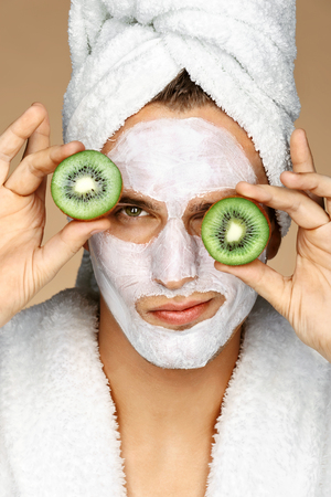 Man with facial mask and kiwi slices on his eyes. Photo of well groomed man receiving spa treatments. Beauty & Skin care concept Stock Photo