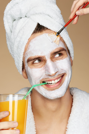Handsome man receiving spa facial treatment. Beautician is applying facial cream on his skin. Beauty & Skin care concept Stock Photo
