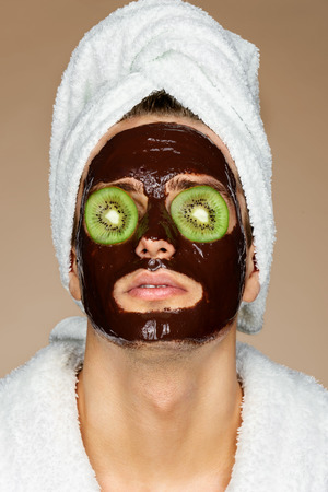 Man with chocolate mack and kiwi slices on eyes. Portrait of handsome man receiving spa treatments. Skin care concept