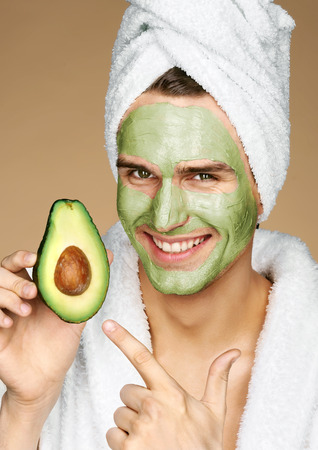 Happy smiling man with facial mask of avocado. Photo of well groomed man receiving spa treatments. Grooming himself Stock fotó