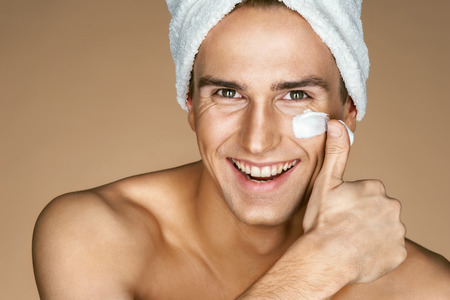 Young man with moisturizer on the face. Photo of smiling man on beige background. Grooming himself Archivio Fotografico