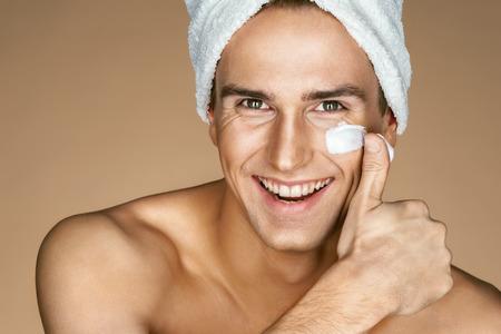 Jonge man met vochtinbrengende crème op het gezicht. Foto van de glimlachende mens op beige achtergrond. Zelf verzorgen