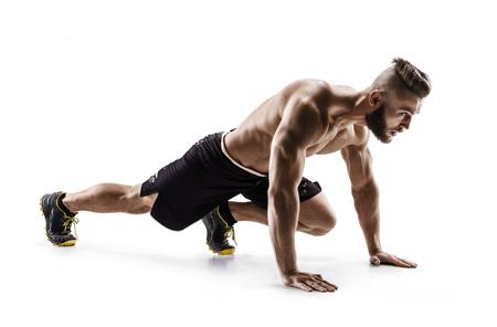 Jonge man doet stretching en warming-up oefeningen. Foto van de gespierde man op witte achtergrond. Sport