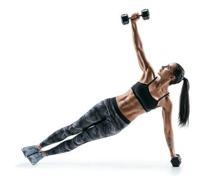 美しく強い女性ダンベル フィットネス板位置の演習を行います。白い背景のシルエットの女性の写真。フィットネスと健康的なライフ スタイルのコ 写真素材