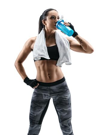 Rusttijd. De aantrekkelijke jonge vrouw in sportenslijtage en met handdoek op schouders drinkt eiwitcocktail in speciale schudbeker. Gezondheid concept.