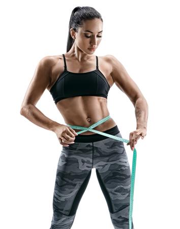 De aantrekkelijke bodybuildervrouw met meetlint meet de grootte van de taille. Foto van jonge vrouw in sportenslijtage op witte achtergrond. Kracht en motivatie
