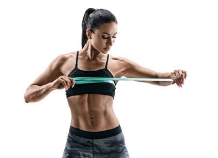 Beautiful athletic woman with tape measures the size of the breast. Photo of young woman in sports wear on white background. Strength and motivation