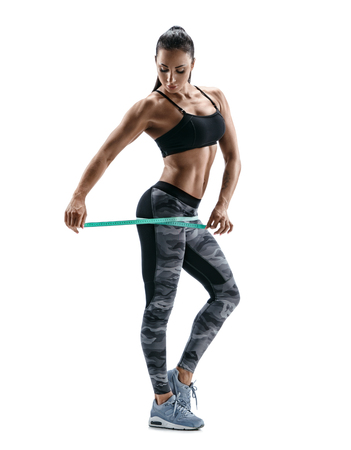 boxing tape: Beautiful bodybuilder woman with tape measures the size of the hips. Photo of  young woman in sports wear on white background. Strength and motivation