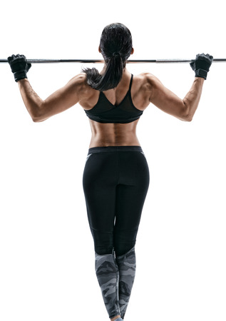 Exercise for the back. Photo of a strong attractive woman doing pull-ups on a white background. Back view.