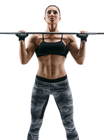 female fitness: Muscular bodybuilder woman doing exercises with barbell over white background. Strength and motivation