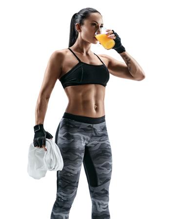 휴식 시간. 매력적인 젊은여자가 스포츠 착용에 수건을 들고 주스를 착용하십시오. 유기농 식품 및 건강 개념입니다.