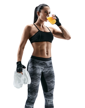 Resting time. Attractive young woman in sports wear holding towel and drink juice. Organic food and health concept. Standard-Bild