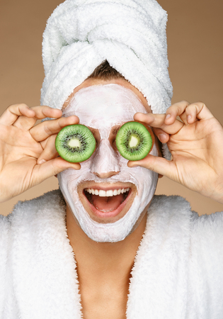 Funny young man with facial mask and pieces of kiwis on eyes. Photo of well groomed man receiving spa treatments. Beauty & Skin care concept Stock Photo