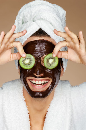 Laughing man receiving spa treatments. Photo of young man with pieces of kiwi in his eyes and chocolate face mask. Beauty & Skin care concept Stock Photo