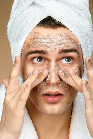 Handsome man cleans face scrub on skin. Close up of young man wearing towel on his head. Grooming himself