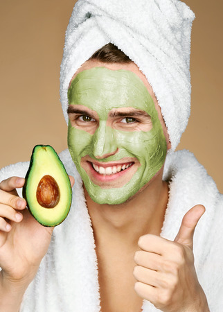 groomed: Portrait of young man wearing facial mask holding slice of avocado and showing thumb up. Happy smiling man receiving spa treatments. Beauty & Skin care concept