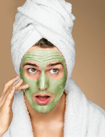 Portrait of man applying avocado facial mask to face. Photo of well groomed man receiving spa treatments. Beauty & Skin care concept