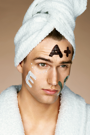Vitamin E, Vitamin A written on mans face. Photo of Well groomed man receiving spa treatments. Beauty & Skin care concept