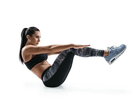 Mooie jonge vrouw die geschiktheidsoefening doet. Foto van gespierde vrouw in silhouet op witte achtergrond. Fitness en een gezonde levensstijl concept Stockfoto