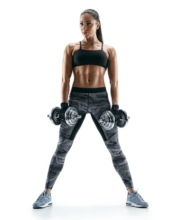 Attractive athletic woman doing a fitness workout with dumbbells. Photo of strong young female on white background. Strength and motivation Stock Photo