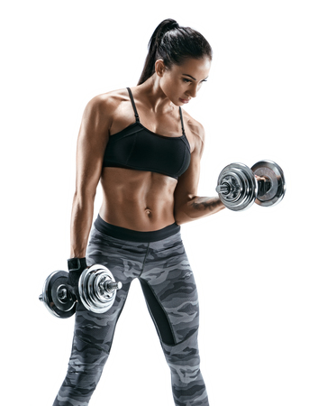 Muscular woman doing exercises with dumbbells at biceps. Photo of strong female isolated on white background. Strength and motivation. Standard-Bild