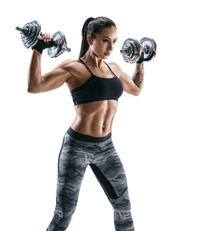 Sportieve vrouw in opleiding pompen spieren van de rug en handen met halters. Foto van atletisch jong wijfje dat op witte achtergrond wordt geïsoleerd. Kracht en motivatie Stockfoto