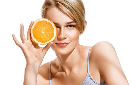Mooi meisje met een plakje sinaasappel voor haar gezicht en lachend. Heerlijk eten voor een gezonde levensstijl Stockfoto