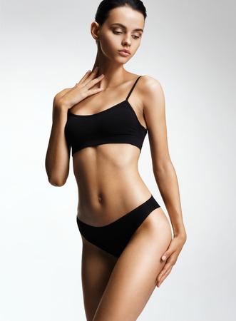 Flawless fashion model in zwarte bikini poseren op grijze achtergrond. Foto van meisje met slank getinkt lichaam. Schoonheids- en lichaamsverzorgingsconcept