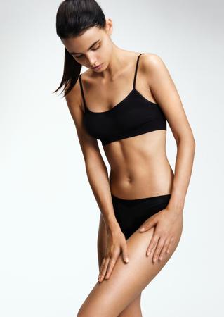 La muchacha hermosa en una ropa interior negro, plantea la delicada piel de sus muslos. Niña con perfecto cuerpo tonificado delgada. Concepto de la salud y la belleza Foto de archivo - 76042779