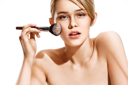 groomed: Woman applying dry cosmetic tonal foundation on the face using makeup brush. Photo of blonde woman isolated on white background. Beauty concept