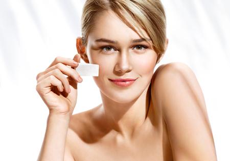 Schitterende vrouw die stichting op haar gezicht toepassen die make-upspons gebruiken. Mooi vrouwengezicht op witte achtergrond. Perfecte make-up