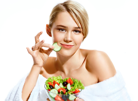 relaxion: Smiling girl enjoying a fresh salad and bites a piece of cucumber. Portrait of girl in bathrobe isolated on white background. Diet concept