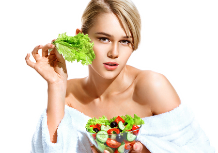 Girl with lettuce leaf. Photo of blonde woman in bathrobe holding vegetable salad isolated on white background. Healthy lifestyle