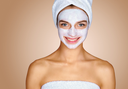 Beautiful young girl with moisturizing facial mask. Photo of smiling girl on beige background. Skin care concept