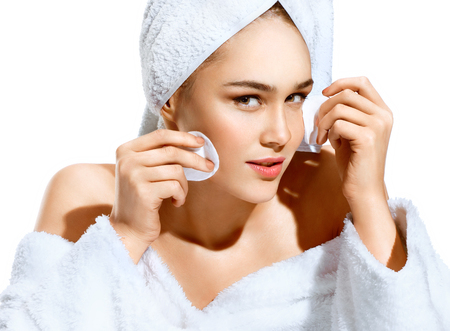Pretty girl removing makeup from her face with cotton pad. Photo of girl after bath in white bathrobe and towel on her head isolated on white background. Skin care and beauty Stock Photo