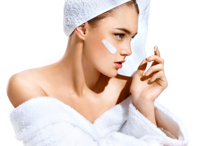 Young woman with flawless skin, applying moisturizing cream on her face. Photo of woman after bath in white bathrobe and towel on white background. Skin care concept Standard-Bild
