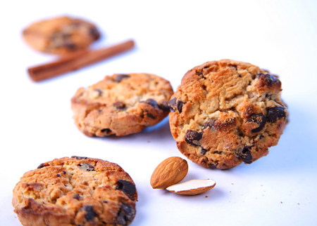 Chocolate chip cookies with almonds and cinnamon on white background. Close up Stock Photo